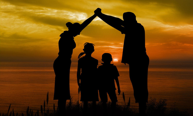 Eltern bilden mit Armen über ihren kindern ein Haus.